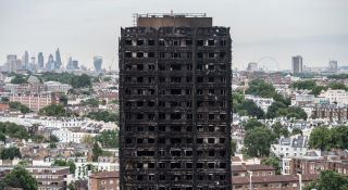 The City of London skyline seen behind the remains of Grenfell Tower in London on June 26. The residential tower block was engulfed in flames in the early hours of June 14.