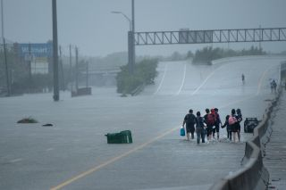 Residents from the Meyerland area of Houston head for an Interstate 610 overpass in an attempt to seek further help during the aftermath of Hurricane Harvey on Aug. 27.
