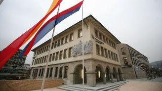A picture of the The Liechtensteinische Landesbank in Vaduz, Liechtenstein, with twin flags blowing in the foreground.