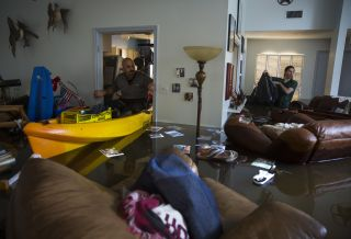 Larry Koser Jr., left, and his son Matthew look for important papers and heirlooms inside Larry Koser Sr.'s house after it was flooded by heavy rains on Aug. 29.