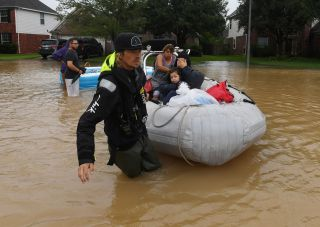 Louisiana resident Andrew Brennan helps evacuate an elderly woman and her granddaughter on Aug. 29 from the Clodine district of Houston.