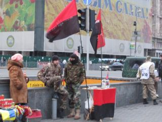 Members of Right Sector stand behind a table set up in Maidan Square next to representatives from the Aidar volunteer battalion collecting money for their group.