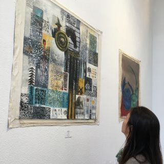 "Stephanie Saldana gazes at ""Untitled"" by Qosai Aizouz, which hangs in the Pages Bookstore Cafe."