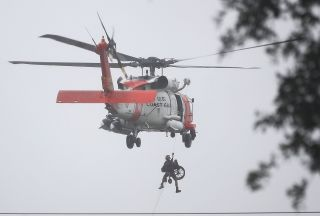 A U.S. Coast Guard helicopter recovers a stranded resident -- and their wheelchair -- from flooding on Aug. 28.