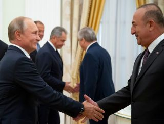 Russian President Vladimir Putin (left) shakes hands with Turkish Foreign Minister Mevlut Cavusoglu before their meeting at the Kremlin in Moscow on Aug. 24, 2018.