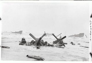 A picture of assault troops on a beach, trying to find cover behind a hedgehog -- three crossed steel beams designed to rip the underside of landing craft as they come onto the beach at high tide.