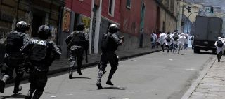 Riot police in La Paz chase medical students, who were protesting changes to Bolivia's malpractice laws.