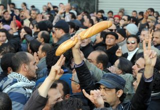 Protesters, one holding bread, shout slogans to show their solidarity with the residents of the Tunisian city of Sidi Bouzid during a demonstration on Dec. 27, 2010 in Tunis.