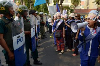 Police in riot gear block the street during a demonstration for International Women's day in Cambodia in 2013.