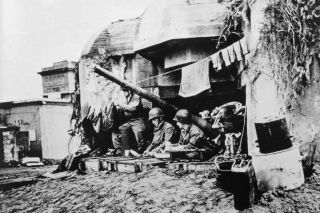 U.S. soldiers dry their clothes in a captured German bunker after Allied forces stormed the Normandy beaches during D-Day.