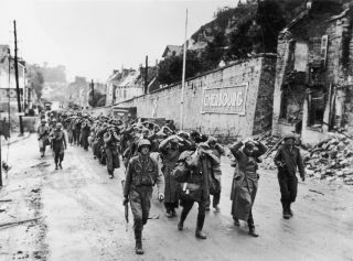 German soldiers pictured being marched through the streets of Cherbourg, France, after the city was liberated by the Americans.