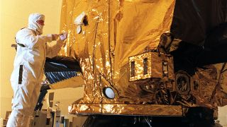 On Aug. 15, 1997, NASA technician Dan Maynard places a CD into a compartment on the Cassini spacecraft at Kennedy Space Center in Florida.