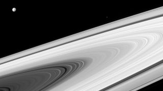 In this image captured by Cassini on April 2, 2016, Saturn's moons Dione (L) and Epimetheus (R) appear above the sunlit side of the planet's rings.