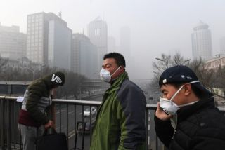 Pedestrians in Beijing brave the smog with the help of masks. During the winter, many cities in northeast China are enveloped in dense smog as residents burn coal and other fuel for heat.