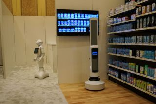 Pepper of SoftBank Robotics (left) and Tally of Simbe Robotics (right) are teaming up to work with retailers. Pepper interacts with customers while Tally scans the shelves to monitor inventory levels in this demo from SoftBank at CES 2019 in Las Vegas on Jan. 8.