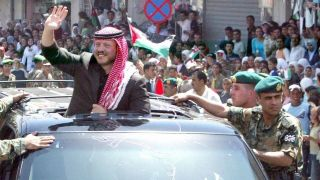 Jordanian King Abdullah II waves to crowds in Madaba during celebrations for the sixth anniversary of his coronation.