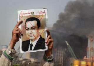 A protester in Tahrir Square holds a photo showing former Egyptian President Hosni Mubarak's face crossed out on Jan. 29, 2011 in Cairo, Egypt during the Egyptian Revolution.