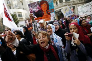 Women in Cairo, Egypt, chant slogans and carry signs during a protest on International Women's Day.