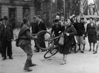 A Russian soldier argues with a German woman in Berlin over a bicycle he wished to buy from her.