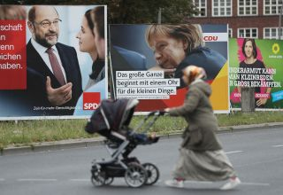 In Berlin, a Muslim woman pushes a pram past campaign billboards that show German Social Democrat candidate Martin Schulz (L), Christian Democratic Union candidate and current Chancellor Angela Merkel (C), and Greens Party co-lead candidate Katrin Goering-Eckardt on Sept. 8, 2017.