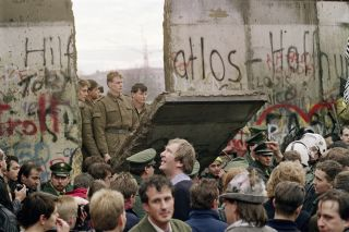 West Berliners crowd in front of the Berlin Wall on Nov. 11, 1989, as they watch East German border guards demolish a section of it.