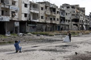 A newlywed couple have their wedding pictures taken in the war-ravaged city of Homs during February 2016.