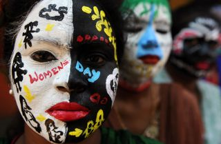 Students at a college in Chennai, India, pose with their faces painted for International Women's day.