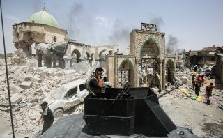 A member of the Iraqi Counter-Terrorism Service (CTS) wipes his face while standing in the turret of a up-armored vehicle parked outside the destroyed gate of Al-Nuri Mosque in the Old City on July 2.