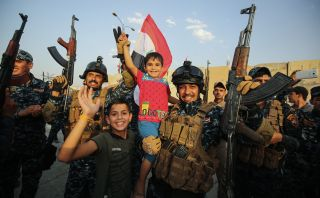 Members of the Iraqi federal police pose for a picture with children during a celebration in the Old City of Mosul during the closing stages of the grueling battle to retake Iraq's second city from Islamic State, July 2.