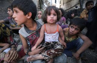A young girl sits on a boy's lap as families wait for the fighting in Mosul's Old City to be over.