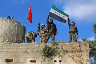 Turkish-backed Syrian rebels, wearing red ribbons, raise a rebel flag as they stand alongside Turkish soldiers on high ground along the Syrian-Turkish border, north of Azaz on Jan. 28, 2018.