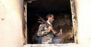 A militant fighting for Libya's Tobruk-based government searches a damaged house in Benghazi.