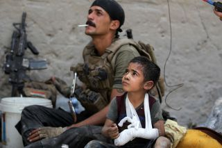 Omar, a young wounded Iraqi boy whose family was killed in the fighting, sits with members of the Counter Terrorism Service (CTS) as they help him escape the Old City, July 3. 2017.