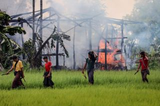 Rakhine Buddhists reportedly have burned thousands of Rohingya houses in western Rakhine state. Several young men walk past a burning structure on Sept. 7.