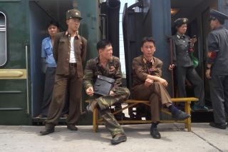 Soldiers of the Korean People's Army relax at Hamhung Railway Station.