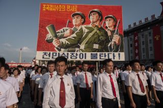 North Koreans assemble under a propaganda poster during a rally for the country's opposition to the United States.