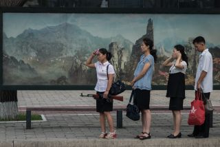 A woman in Pyongyang holds a fake rifle while waiting for a trolley bus.