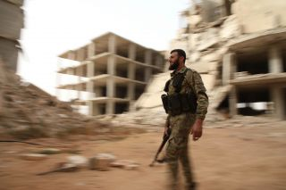 A Syrian rebel fighter from the National Liberation Front walks down a street in the rebel-held al-Rashidin district of western Aleppo's countryside near Idlib province on Oct. 15, 2018.
