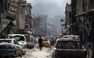 A man walks by destroyed vehicles in the Old City of Mosul, July 2.