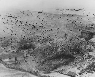 Taken from a circling aircraft, a picture shows hundreds of American paratroopers dropping into Normandy on D-Day, June 6, 1944.
