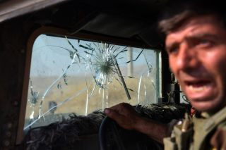 A Kurdish Peshmerga fighter reacts to hits against his vehicle from Islamic State snipers located in the small town of Bartella just outside Mosul.