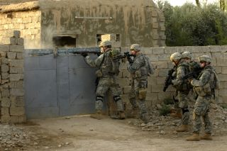 U.S. Army soldiers with the 82nd Airborne Division breach the gate of a house during a mission in Iraq during July 2007.