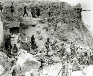 Lt. Col. James E. Rudder consolidates his forces and processes prisoners of war after the assault up the cliffs of Pointe du Hoc by the 2nd Ranger Battalion (D, E and F Company).