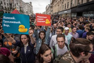 "Anti-corruption protesters march in Moscow on June 12 holding posters that read ""corruption steals the future"" and ""miserable cowardly thief."""