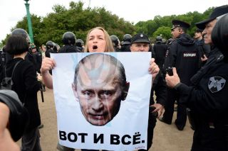 "A woman holds a poster bearing an image of Putin with the words ""that's all"" in central St. Petersburg on June 12."