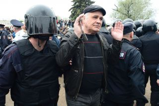 Russian police officers detain a protester in St. Petersburg on June 12.