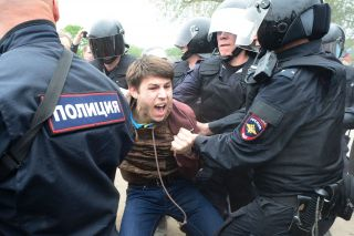 Police officers restrain an angry young protester in the St. Petersburg rally on June 12.