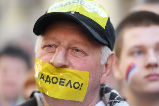 An opposition supporter wearing tape over his mouth waits in line outside of Russian President Vladimir Putin's administrative office during a protest in Moscow on April 29.
