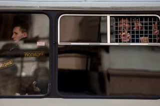 Detainees gesture from a police bus after being taken into custody during the March 26 anti-corruption protest in Moscow.