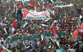 Syrians chant slogans and wave opposition and Turkish national flags during a demonstration against the Syrian government in the rebel-held town of Maarat al-Nuaman in the north of Idlib province on Sept. 21, 2018.